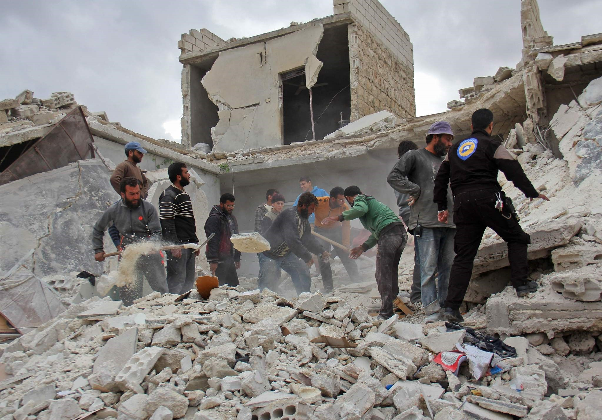 Rescuers and civilians inspect a destroyed building in the Syrian village following air strikes by Syrian and Russian warplanes on November 16, 2016. (AFP Photo)