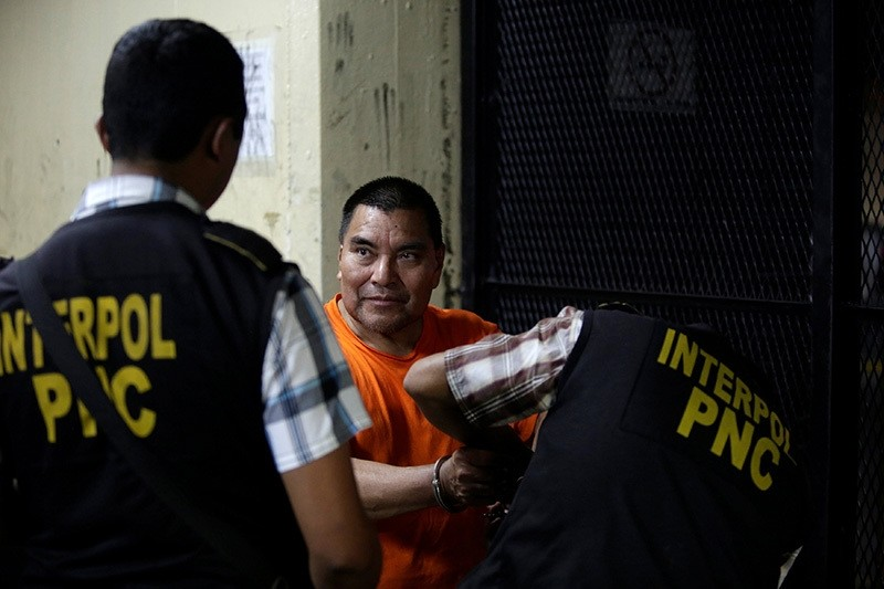 Santos Lopez Alonzo is being handcuffed by an Interpol agent while waiting for a judge's hearing after having been deported from the U.S., in Guatemala City, Guatemala, August 10, 2016. (Reuters Photo)
