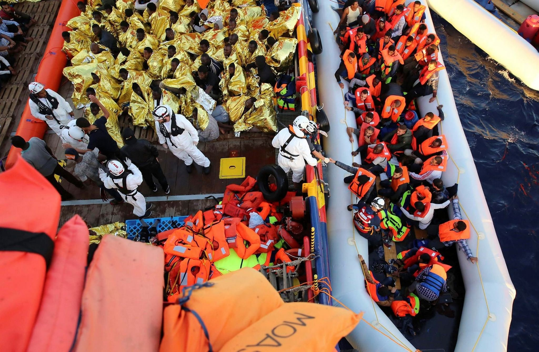 Migrants cover themselves with emergency blankets after being rescued by the vessel Responder. (AP Photo)