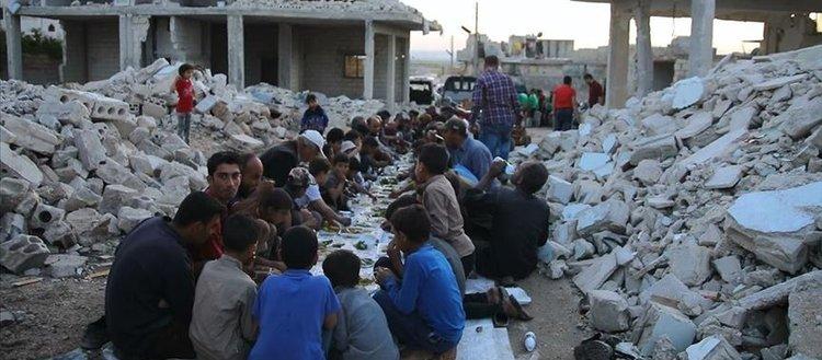 Suriye'de enkaz haline gelen evlerin arasında toplu iftar