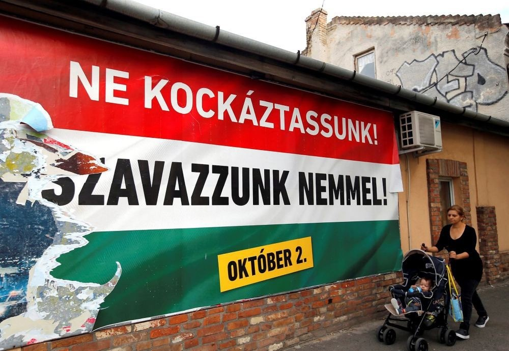 A woman pushes a stroller with her child in front of the Hungarian governmentu2019s poster in Budapest, Hungary, Sept. 28. The poster reads: u201cWe should not take a risk, vote no (to refugees).u201d  (REUTERS Photo)