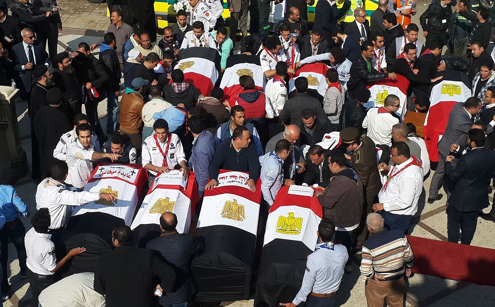 Egyptian mourners and officials stand next to the coffins of the victims of a bomb explosion that targeted a Coptic Orthodox Church in Cairo. (AFP Photo)