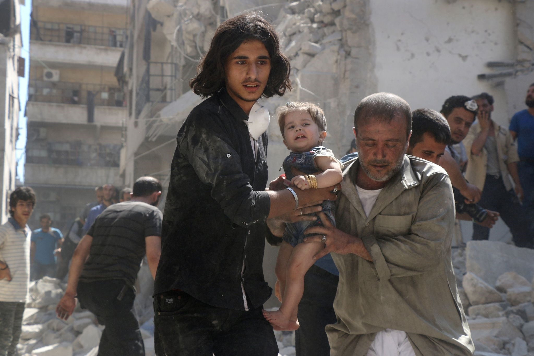 A Syrian civil defence member and a volunteer carry a little girl rescued from under the rubble of destroyed buildings in Aleppo, on September 10, 2016. (AFP Photo)