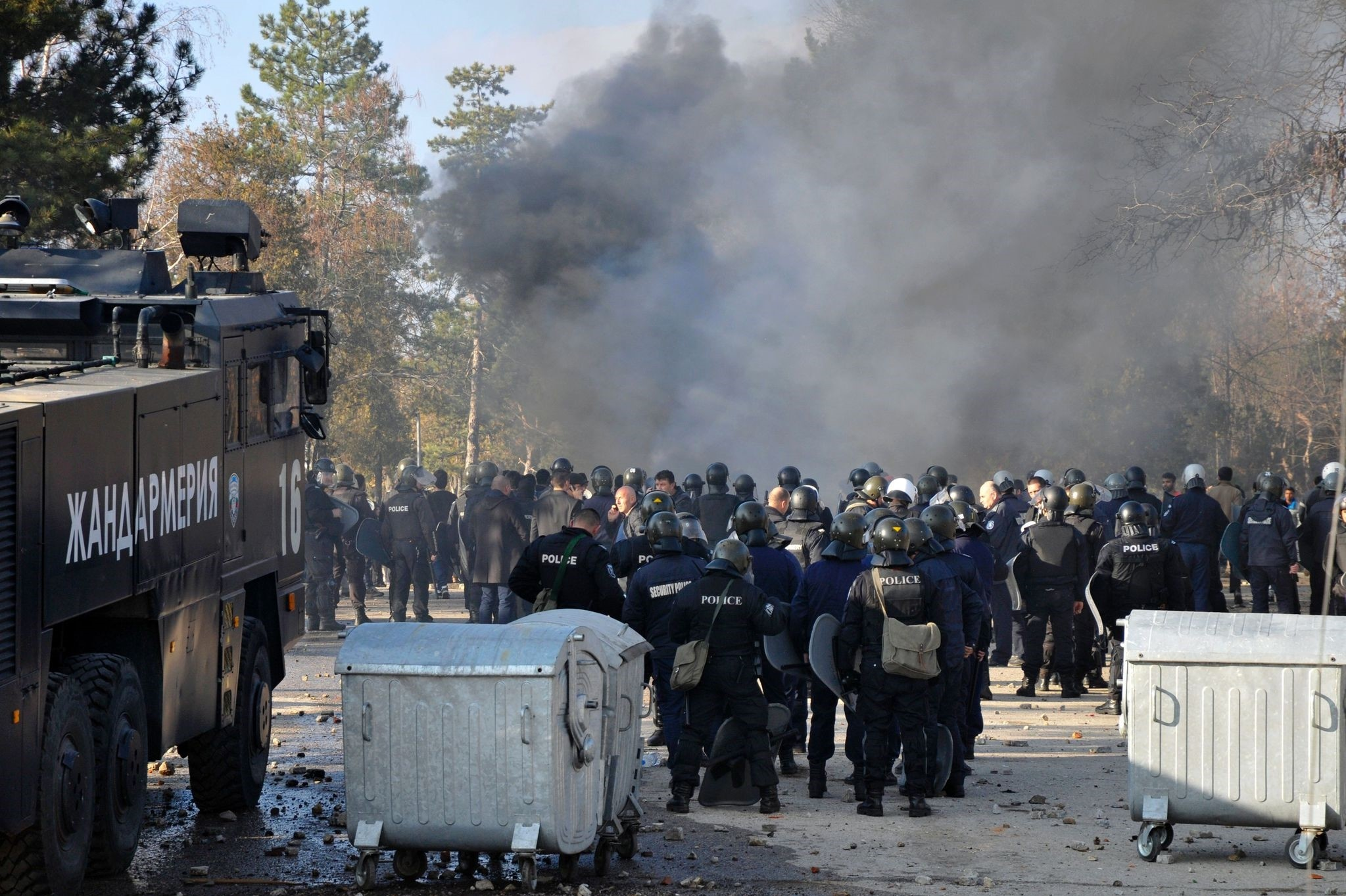 Bulgarian riot police stand near garbarge bins during clashes in the migrants reception centre in the town of Harmanlu0131 on November 24, 2016. (AFP Photo)