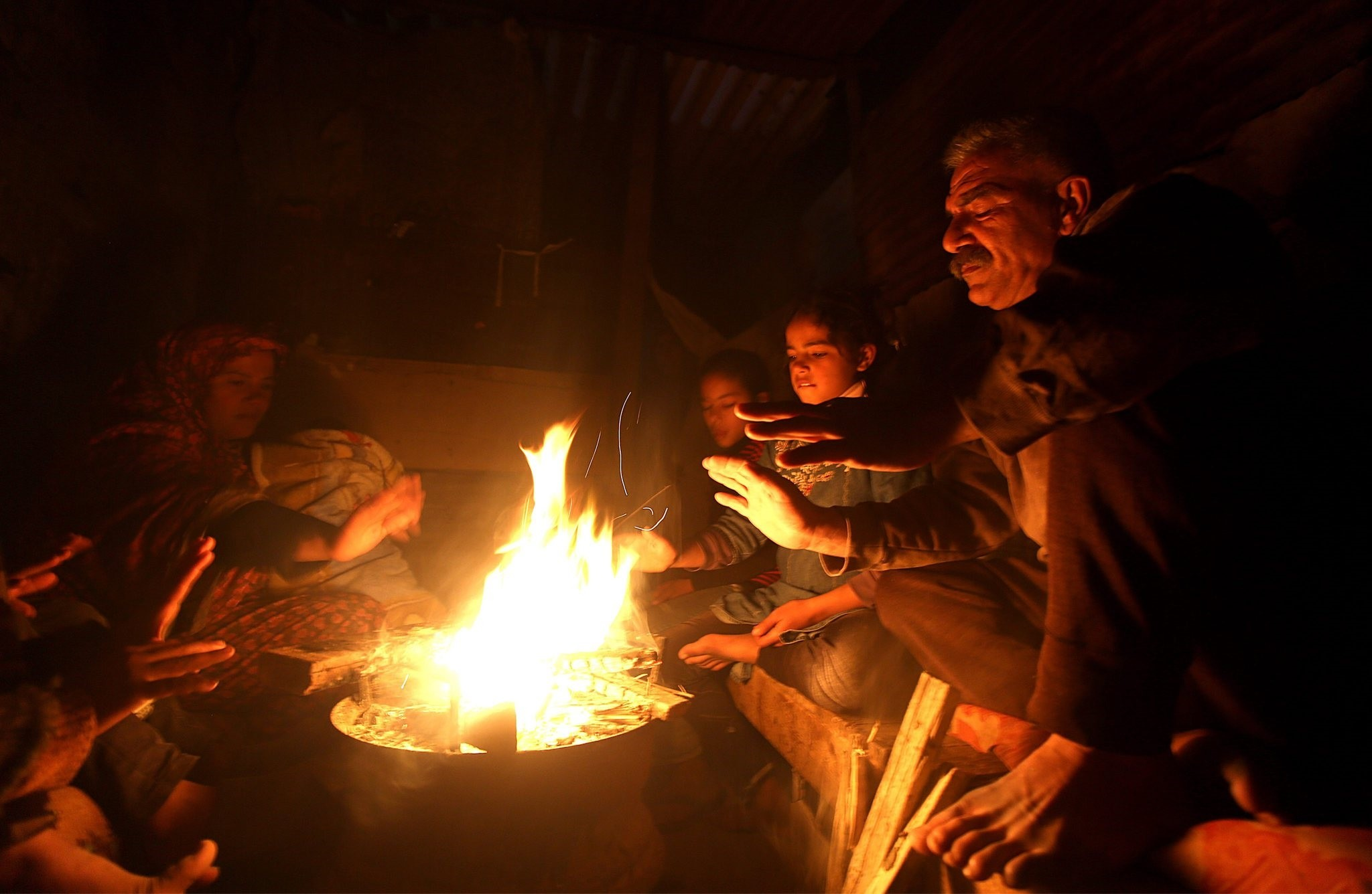 Palestinians warm up in front of a fire outside their makshift house during a power outage in Al Zaitun neighbourhood in the east of Gaza City, 11 January 2017. (EPA Photo)