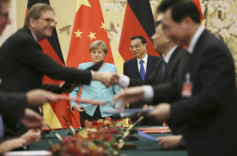 Angela Merkel (back, L) and Chinese Premier Li Keqiang (back, R) look on as delegates exchange documents during signing ceremony at the Great Hall of the People in Beijing (EPA)