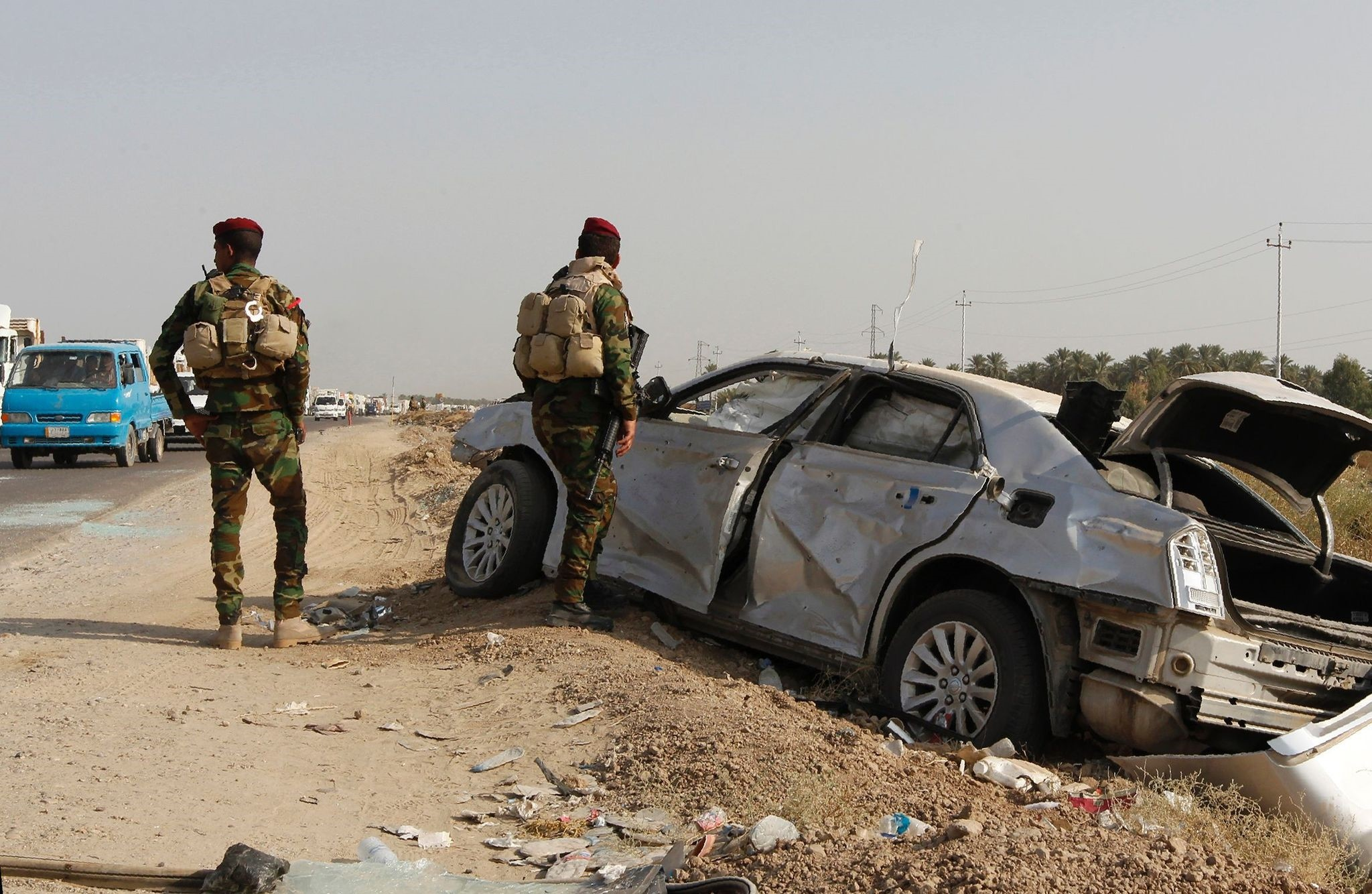 Iraqi government forces stand next to a damaged vehicle at the site of car bomb explosion targeting an Iraqi army checkpoint in Yusufiya, south of the capital Baghdad, on October 17, 2016. (AFP Photo)