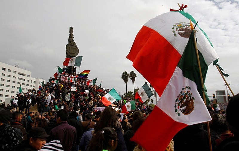 Demonstrators hold Mexico's flags and posters during a protest against a fuel price hike in Tijuana, Baja California state, Mexico January 22, 2017 (Reuters Photo)