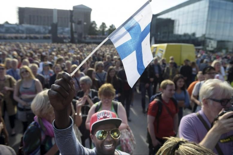 Mire Ibrahim waves the Finnish flag during a demonstration against racism where an estimated 15,000 people attended in Helsinki, Finland on July 28th, 2015. (REUTERS Photo)