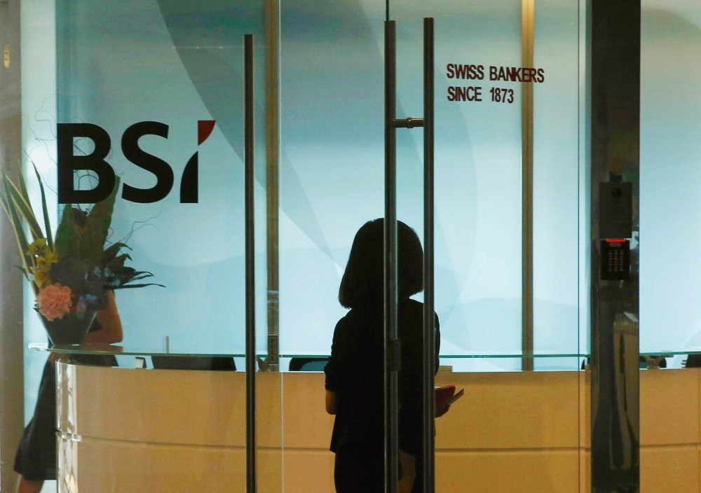 An employee enters the reception area of Swiss bank BSI's office in Singapore.