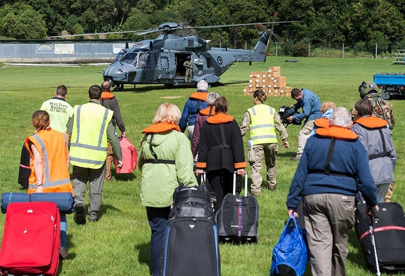People walking to a helicopeter with their suitcases as hundreds are evacuated from Kaikoura, New Zealand. (AFP Photo)
