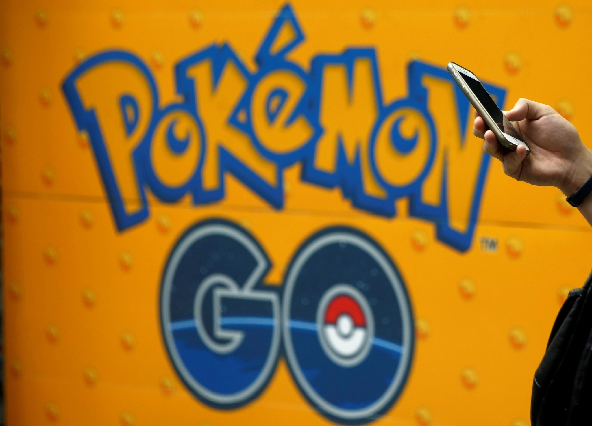 A man uses a mobile phone in front of an advertisement board bearing the image of Pokemon Go at an electronic shop in Tokyo, Japan, July 27, 2016. (REUTERS Photo)