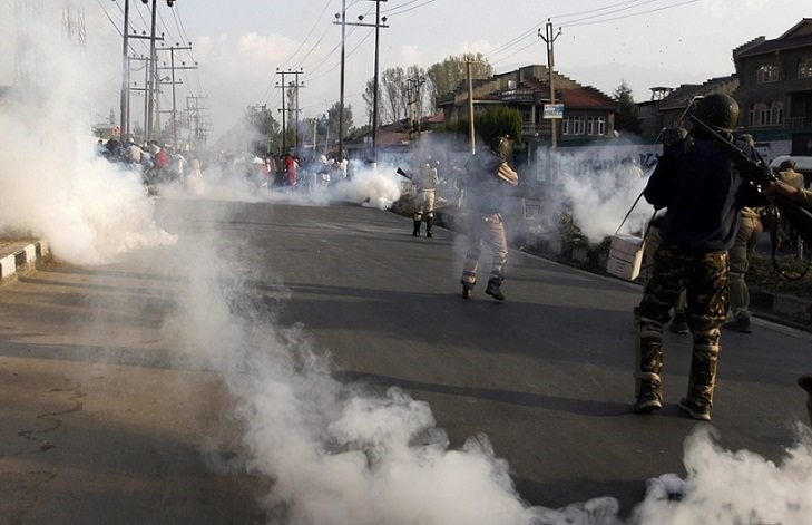 Kashmiri Muslims hold the body of Junaid Ahmad, 13, amid tear smoke fired by Indian police during his funeral procession in Srinagar, the summer capital of Kashmir, Oct. 8 2016. (EPA Photo)