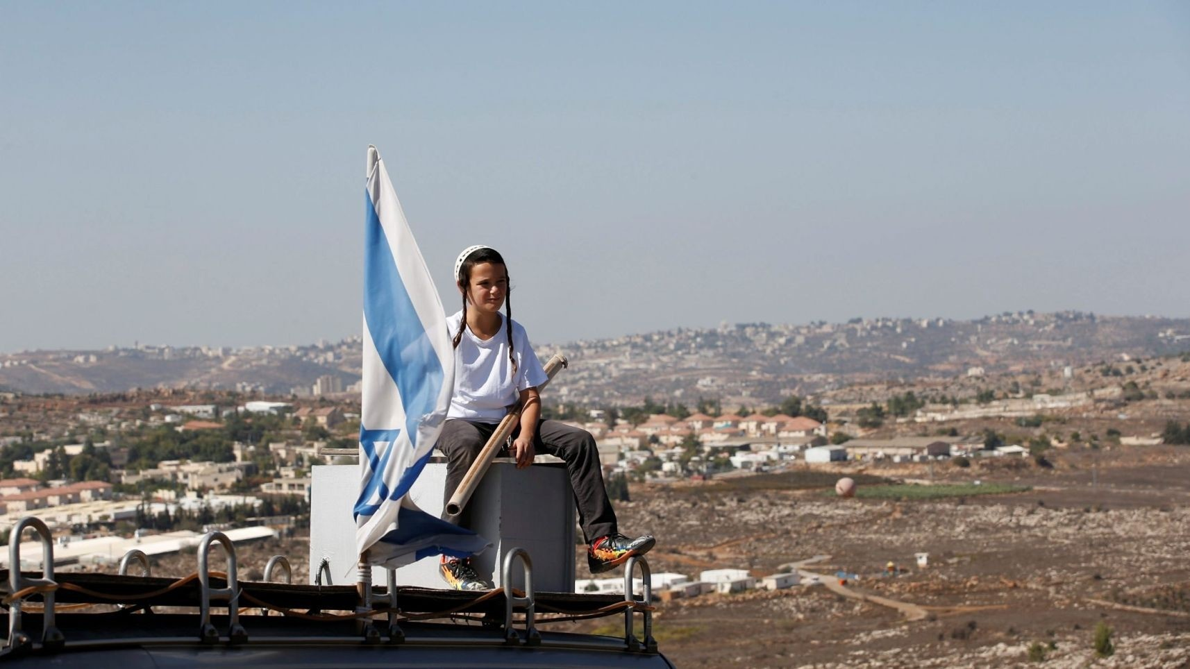 A boy sits on the roof of a vehicle at the entrance to the settler outpost of Amona in the West Bank (Reuters Photo)