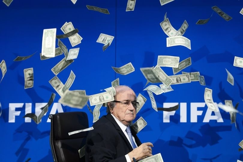 A prankster showers Sepp Blatter with fake dollars at FIFA headquarters in July 2015 (AFP Photo)