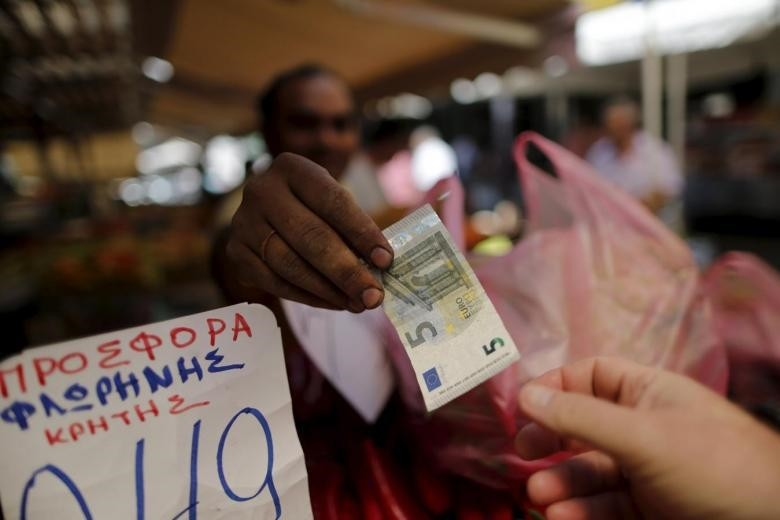 A vendor gives a five Euro bank note back to a customer at the central market in Athens, Greece.