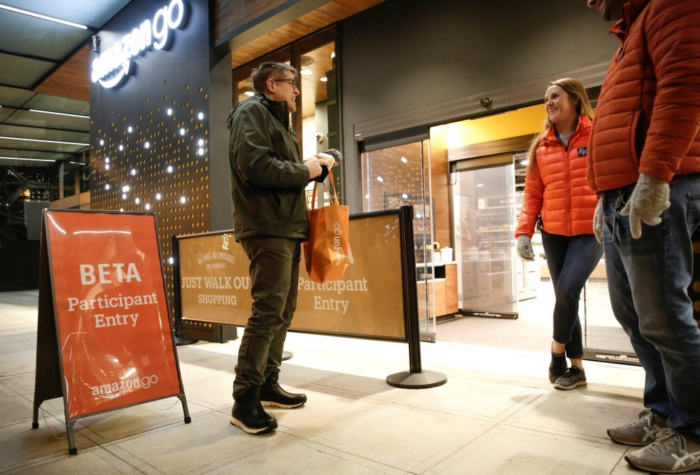 Amazon employees are pictured outside the Amazon Go brick-and-mortar grocery store without lines or checkout counters, in Seattle Washington.