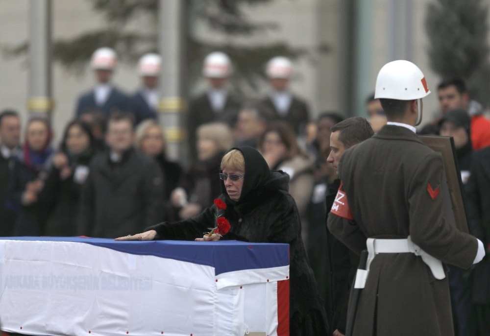 Late Russian Ambassador to Turkey Andrei Karlov's wife Marina reacts next to the flag-wrapped coffin during a ceremony at Esenboga airport in Ankara, Turkey, Dec. 2016.