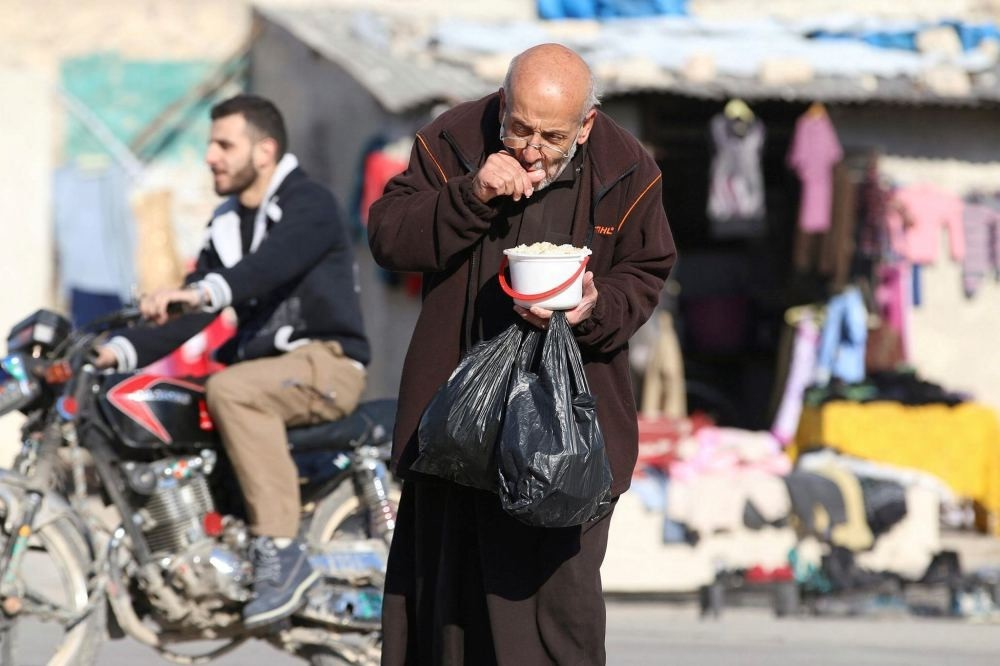 A man eats food that was distributed as aid in an opposition-held besieged area in Aleppo, Syria, Nov. 6.