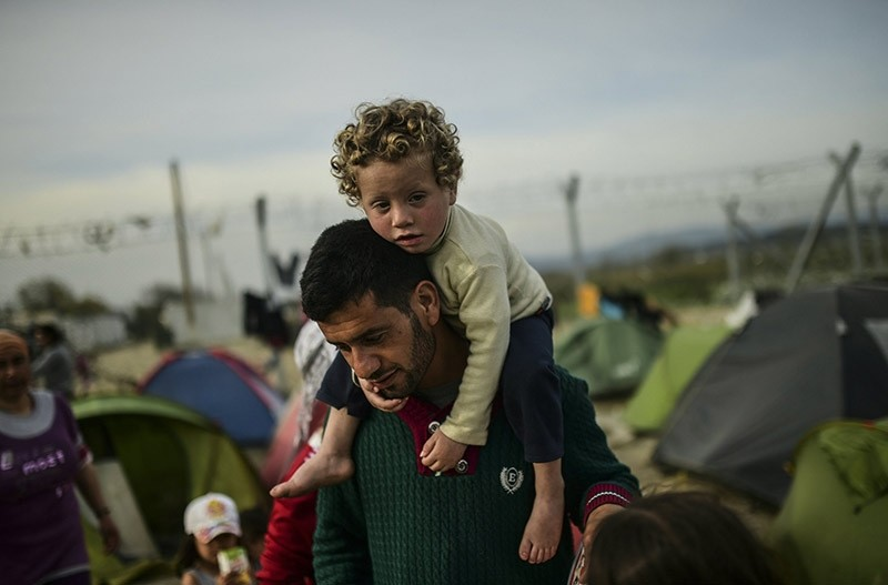 A man carries a child as migrants and refugees carry on with their daily lives at the makeshift camp along the Greek-Macedonian border, on April 1 2016. (AFP Photo)