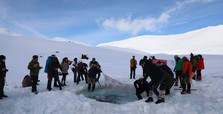 Daredevils dive into glacial lake, brave the cold