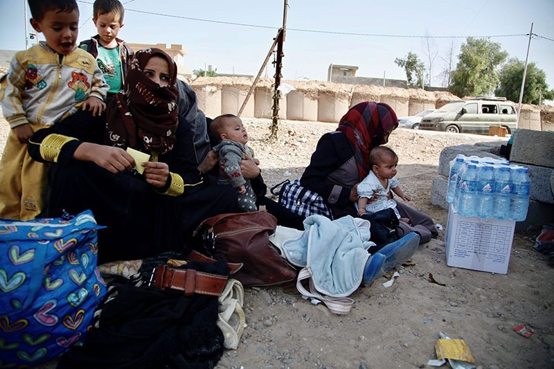 A handout picture release by Save The Children shows displaced Iraqi women, who fled the Islamic State (IS) group held Hawijah area, sitting with their children before being screened at the Dibis checkpoint (AFP Photo)