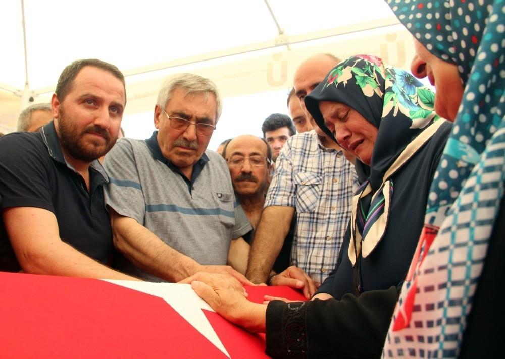 Cengiz Hasbalu2019s family mourn over his flag-draped coffin. (IHA Photo)