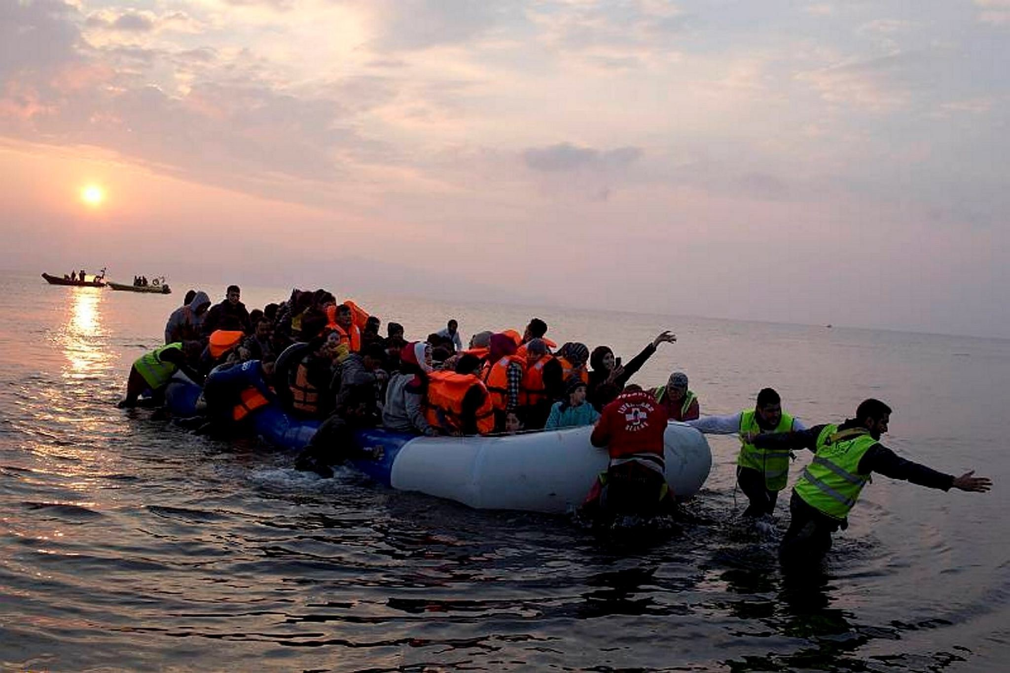 In this March 20, 2016 file photo, volunteers help migrants and refugees on a dingy as they arrive at the shore of the northeastern Greek island of Lesbos, after crossing the Aegean sea from Turkey.