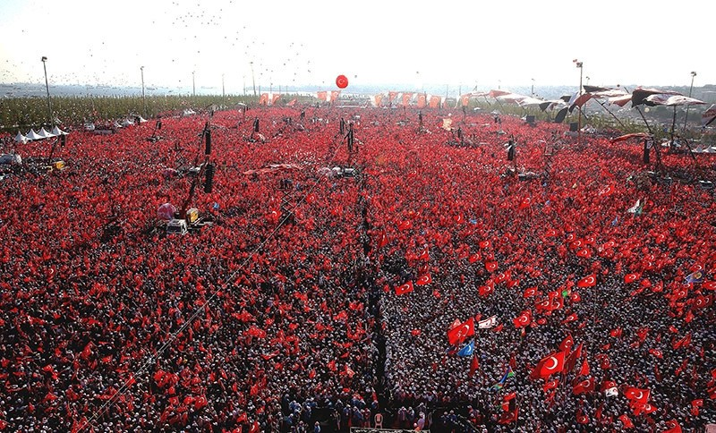 People wave Turkish flags and picture of Turkish President Recep Tayyip Erdou011fan during a rally to protest the failed coup attempt on 15 July 2016. (IHA Photo)