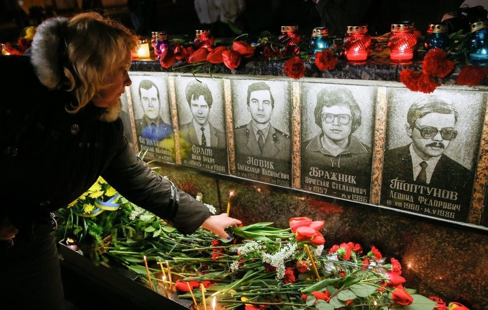 A wdman lays flowers at the memorial the u2018liquidators' who died during clean up after the Chernobyl nuclear power plant disaster, during a ceremony in Slavutich, Ukraine.
