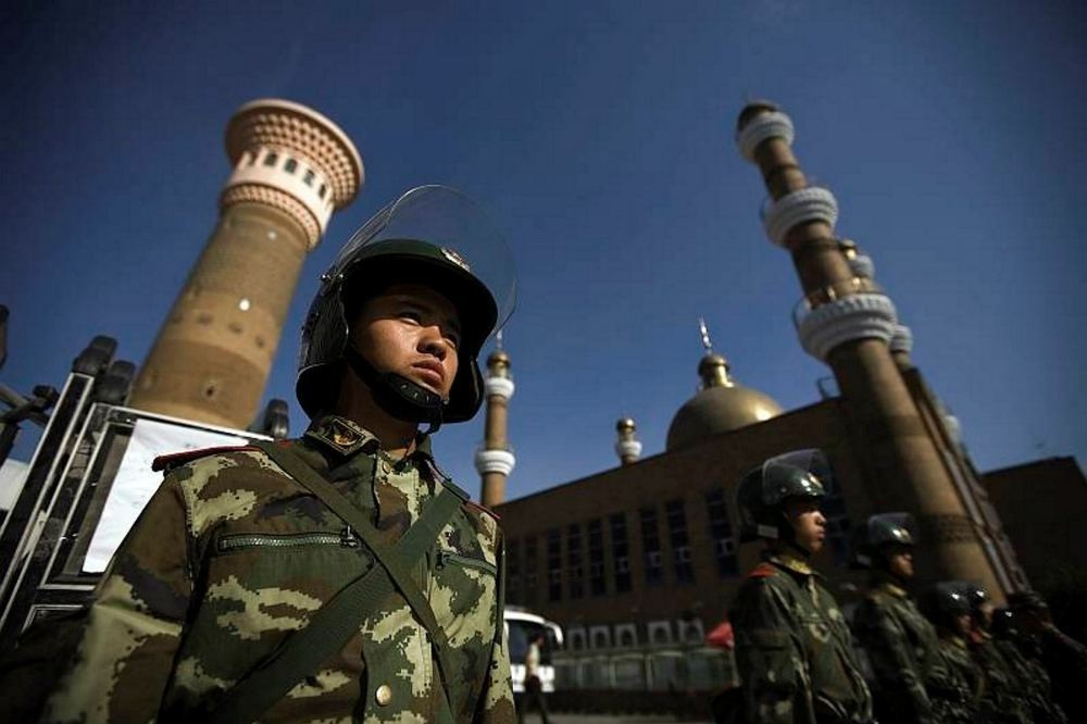 Chinese security forces patrol the entrance to a historic mosque in Xinjiang.