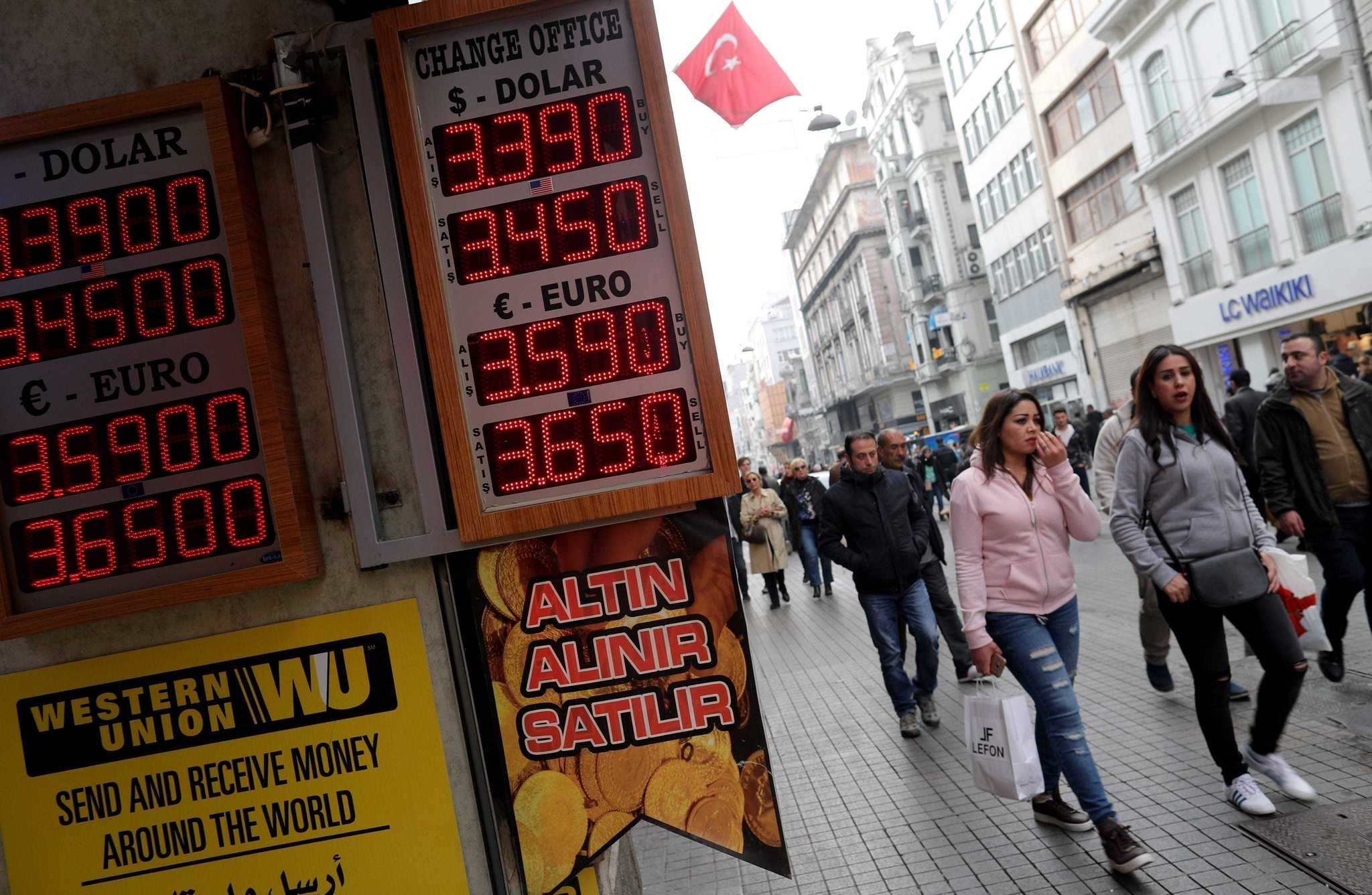 People walk near an exchange office on Istiklal Street in Istanbul.