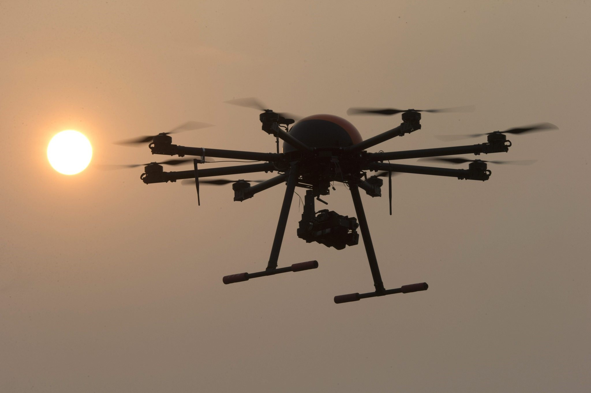 a drone hovers with the sun in the background near a school run by TT Aviation Technology in Beijing. (AP Photo)