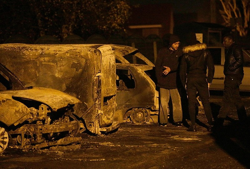 People stand near burnt cars on the street after protesters clashed with police in Beaumont-sur-Oise, north of Paris early on Nov. 24, 2016. (AFP Photo)