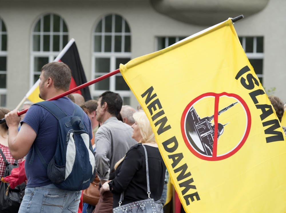 A supporter of the right-wing organization, Patriotic Europeans say No, PEsN, holding a flag reading ,Islam, no thanks, during a rally in Erfurt, central Germany, June 4, 2016.