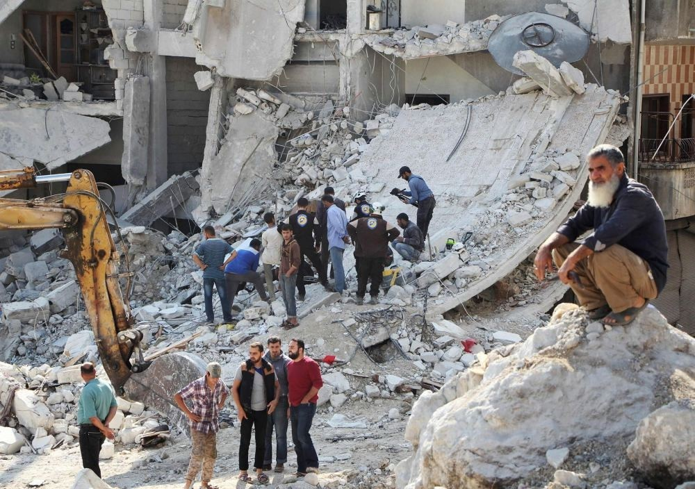 Syrian civil defense volunteers search for victims amid the rubble of destroyed buildings on Oct. 24, following overnight air strikes in the opposition-held town of Kafar Takharim, in the Idlib province of northwest Syria.