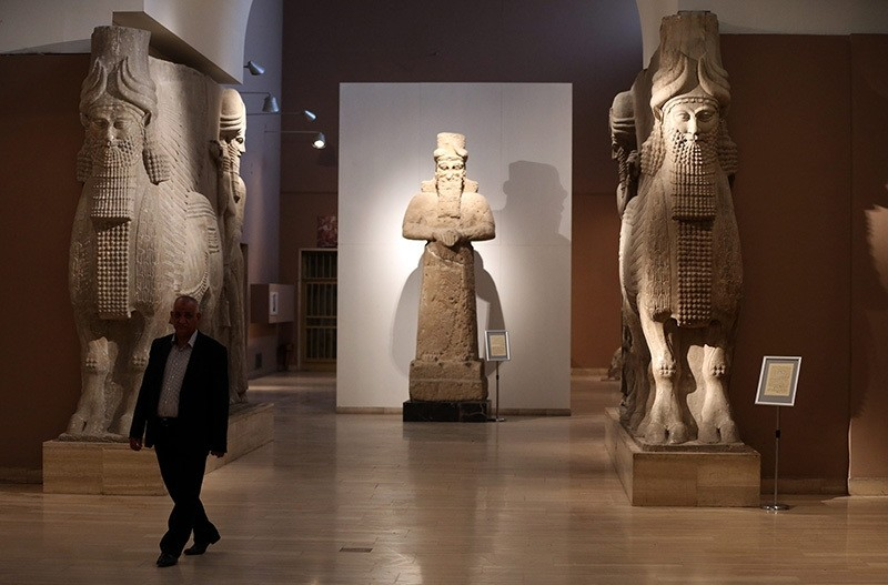 A man at Iraq's National Museum in Baghdad walks past two ancient Assyrian human-headed winged bull statues, March 1, 2015. (AP Photo)