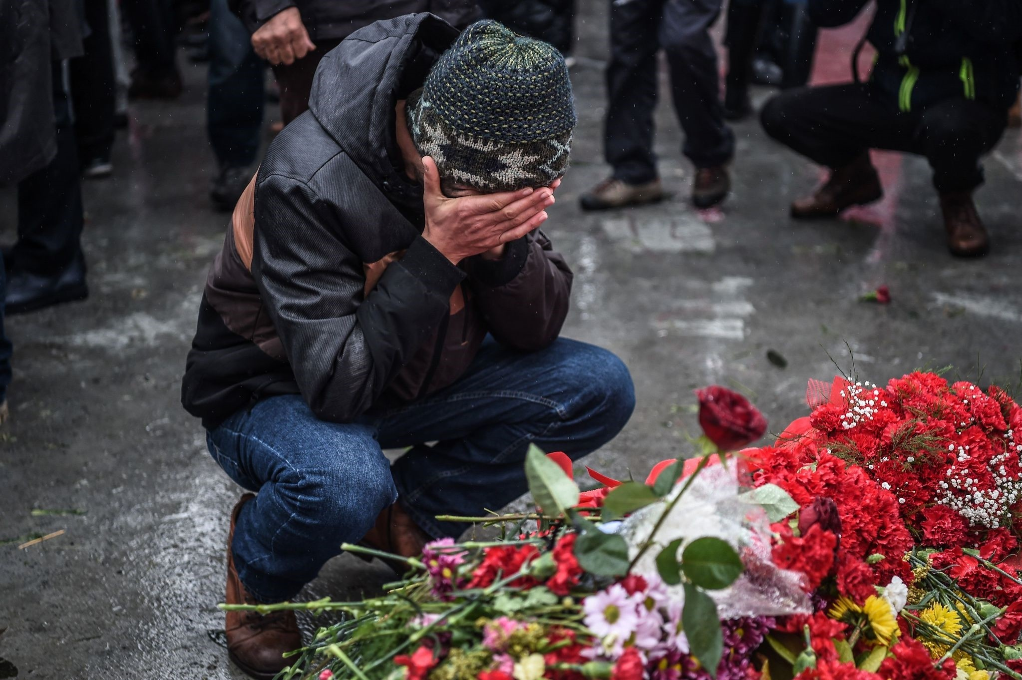 A grieving man reacts before the flowers laid for victims at the site of blasts.