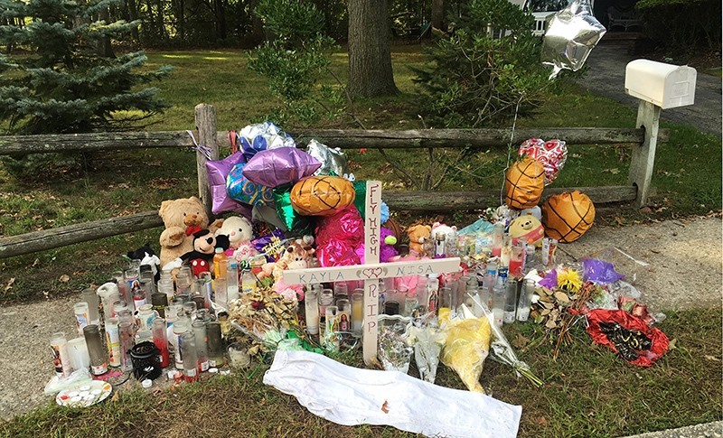 In this Sept. 27, 2016 photo, a memorial for Nisa Mickens and Kayla Cueva is located near the locations where their bodies were found in Brentwood, N.Y. (AP Photo)