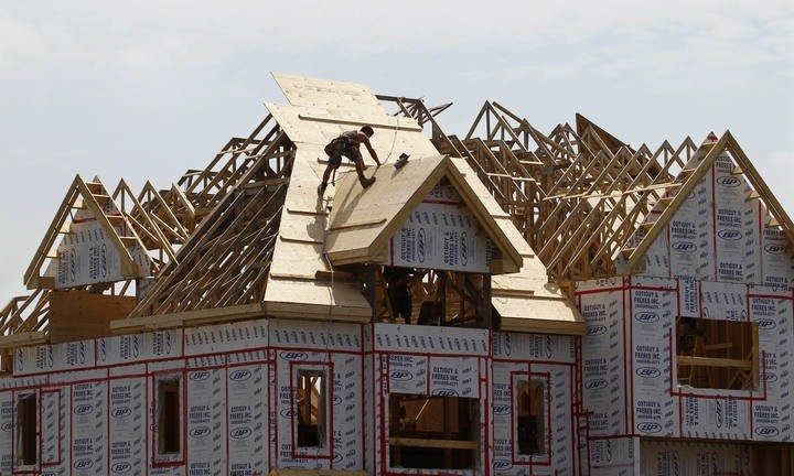 A builder works on the the roof of a new home under construction in the Montreal (Reuters Photo)