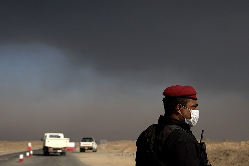 A member of the Iraqi special forces guards a checkpoint near the village of Awsaja, Iraq, as smoke from fires lit by Daesh at oil wells and a sulfur plant fill the air on Saturday, Oct. 22, 2016. (AP Photo)