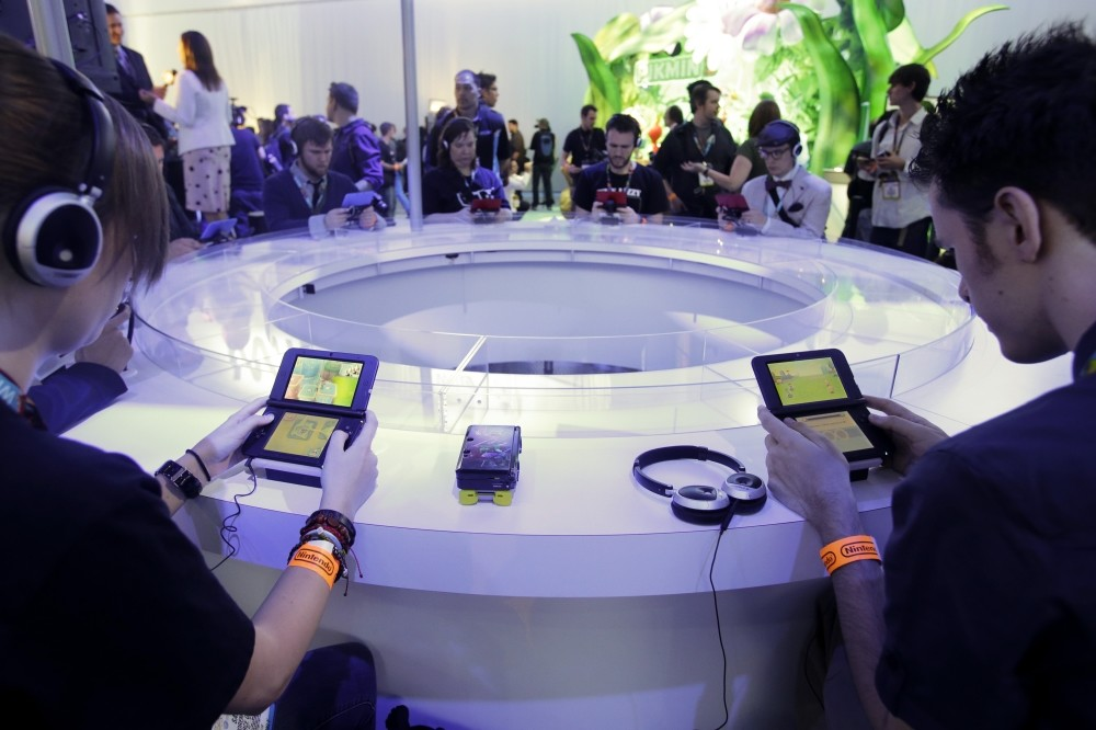 Attendees play video games on the Nintendo 3DS at the Nintendo Wii U software showcase during the E3 game show in Los Angeles.