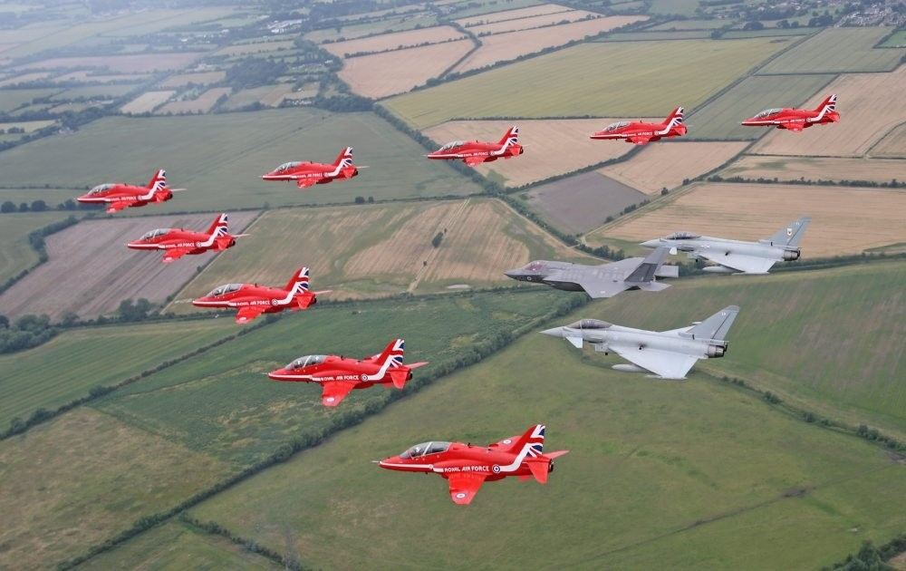 Jet aircraft from the British Royal Air Force Aerobatic Team, the Red Arrows, in formation with two Typhoons and the F-35B Lightning II over Gloucestershire.