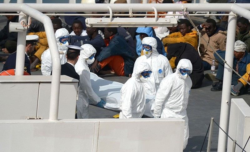 This file photo taken on April 20, 2015 shows rescued migrants watching as the body of a person who died after a fishing boat carrying migrants capsized off the Libyan coast (AFP Photo)