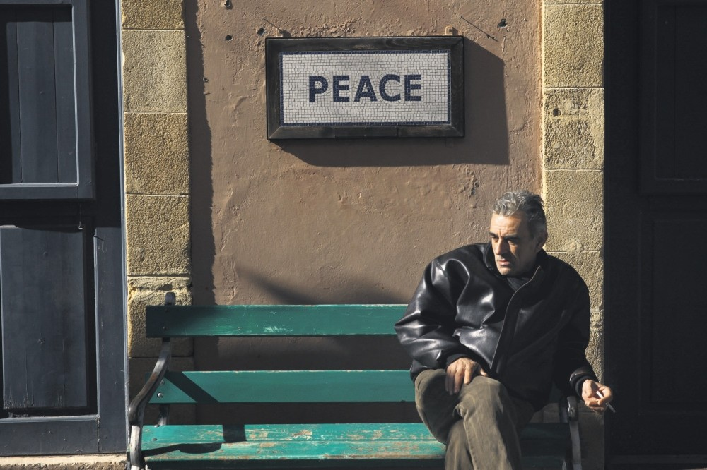 A man sits on a bench under a peace sign near the UN-controlled buffer zone in Nicosia, Cyprus January 9, 2017. (Reuters Photo)