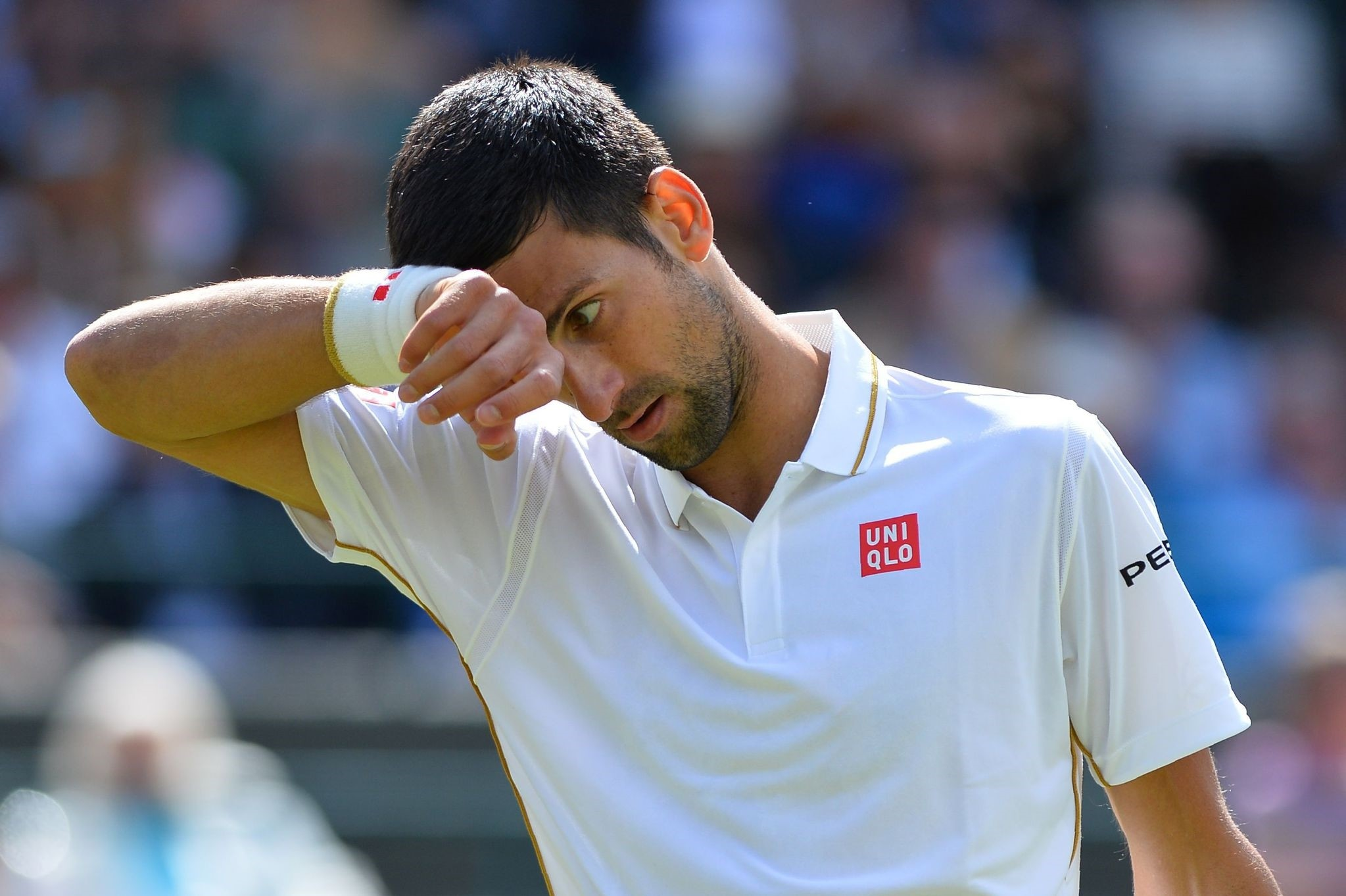 Serbia's Novak Djokovic wipes his brow while playing US player Sam Querrey during their men's singles third round match on the sixth day of the 2016 Wimbledon Championships. (AFP Photo)